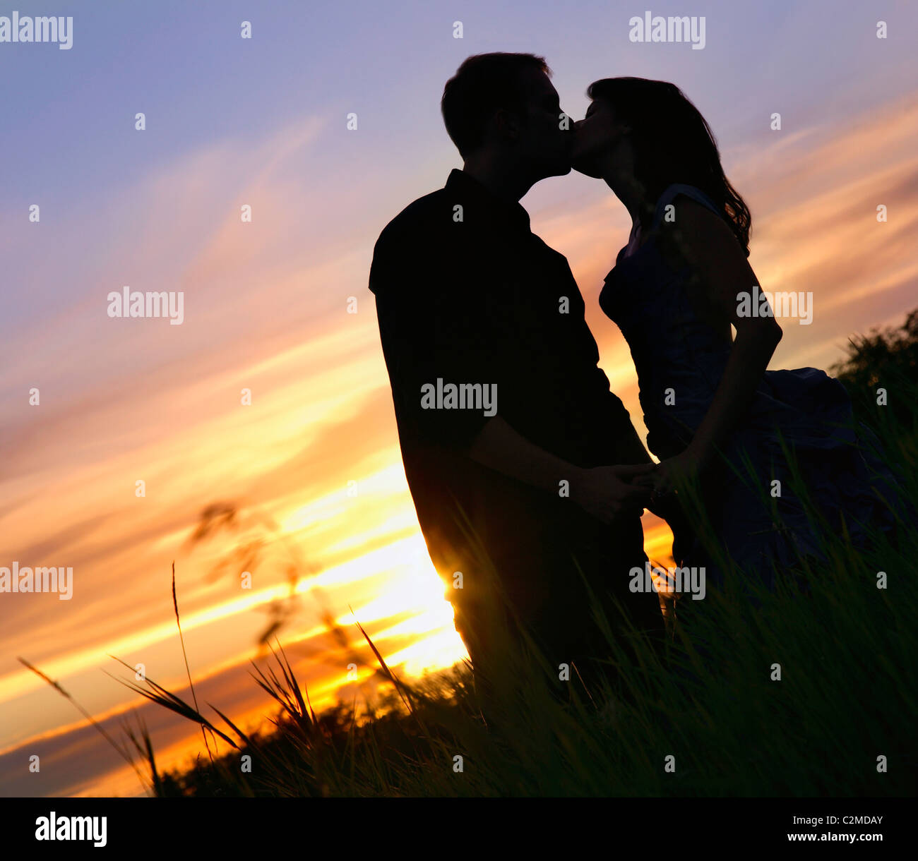 Happy Couple Sitting On Sandy Beach Embracing Kissing: Silhouette Of Man And Woman Kissing Stock Photos