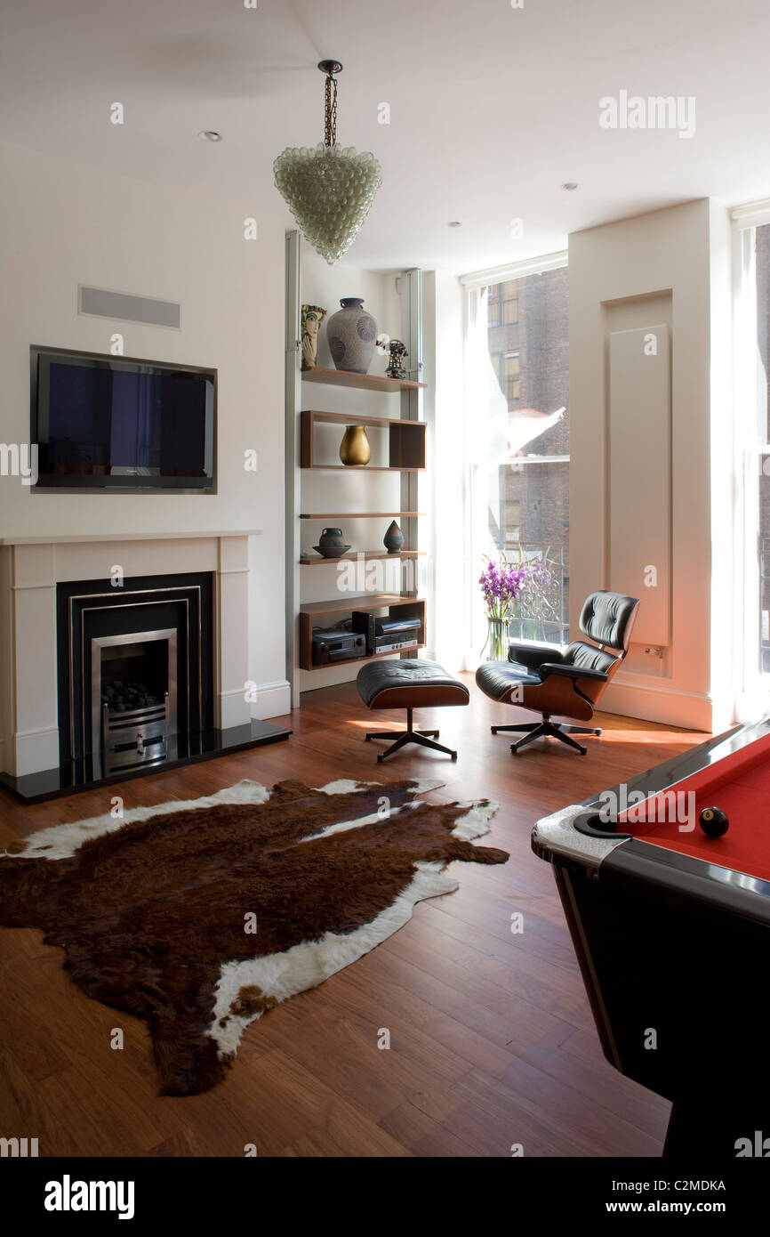 Living room with cow hide rug and Eames chair. - Stock Image