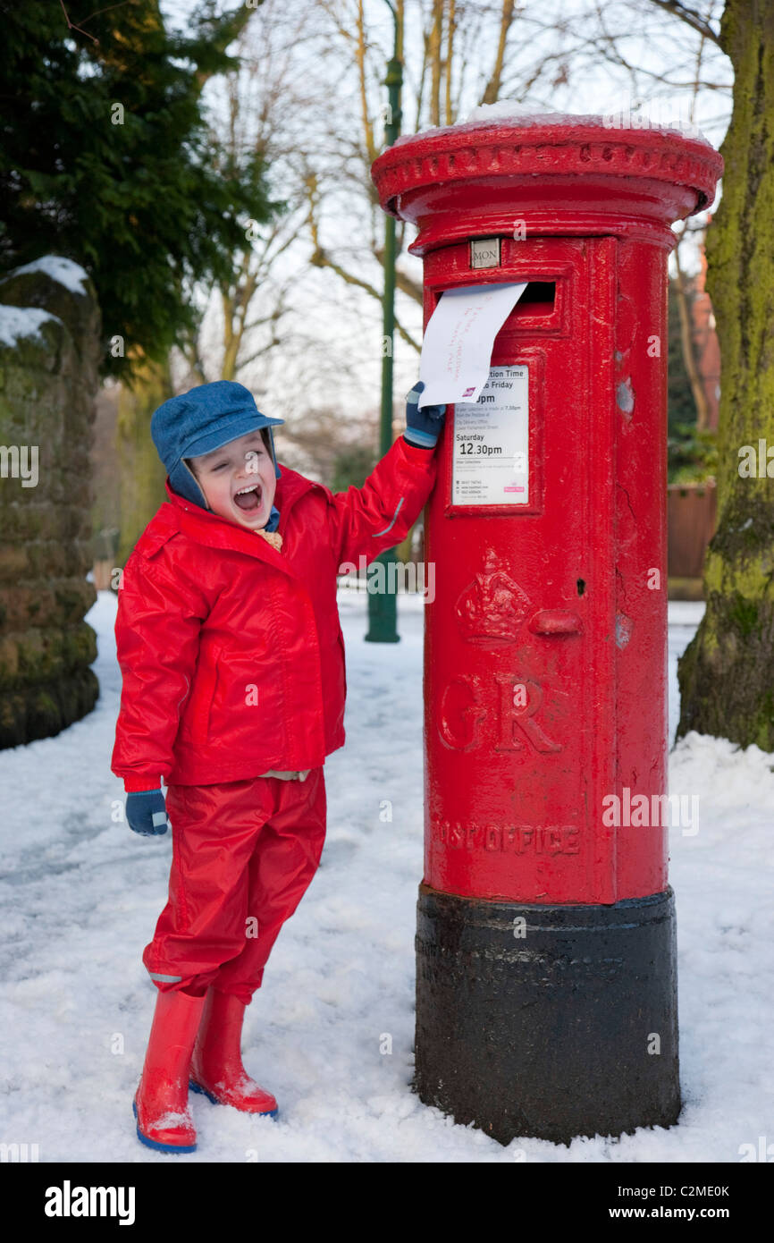 Posting a letter to Santa, England.Post box, Letter box, snow - Stock Image