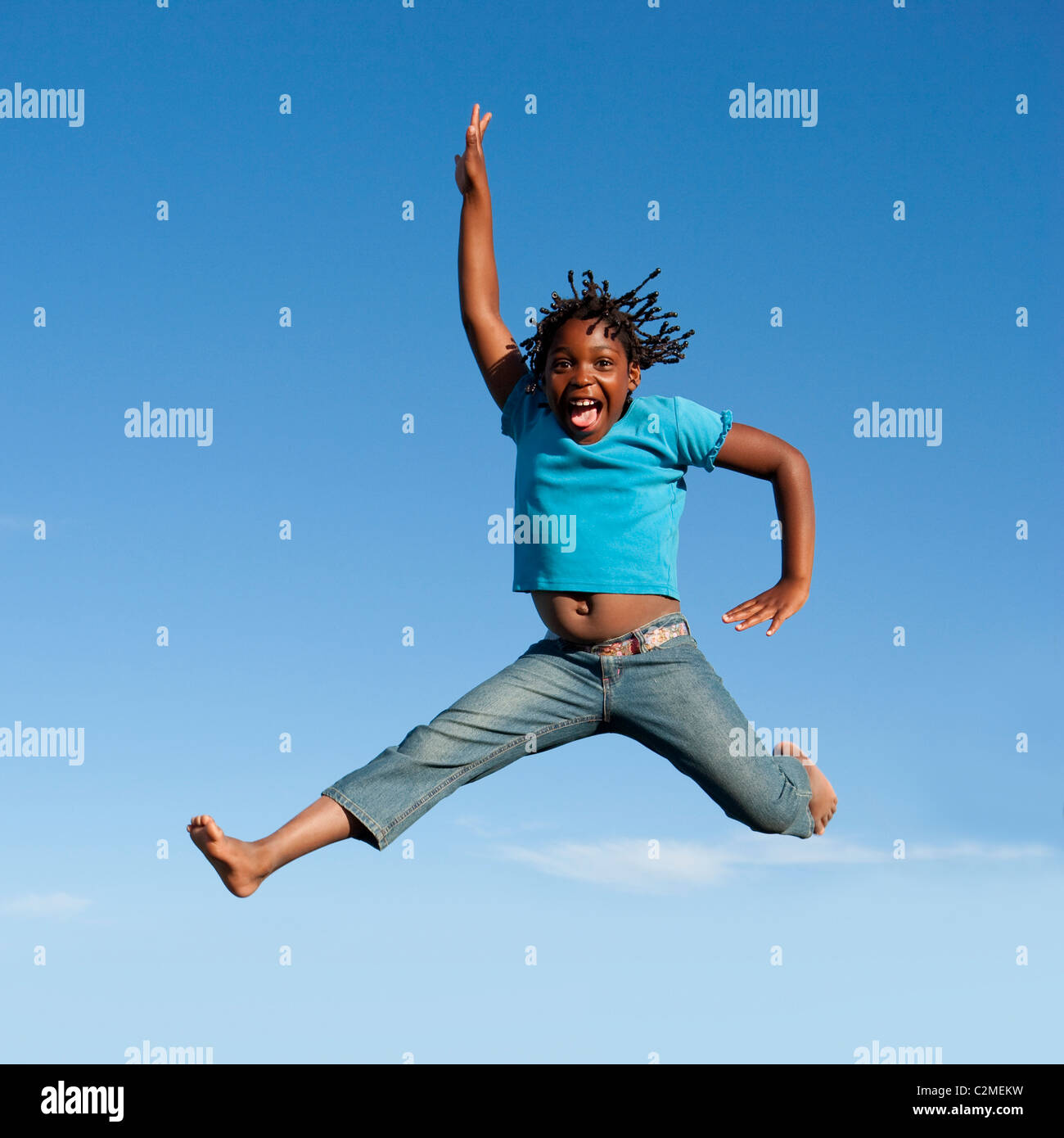 Jumping For Joy; Girl Jumping In Mid-Air Stock Photo