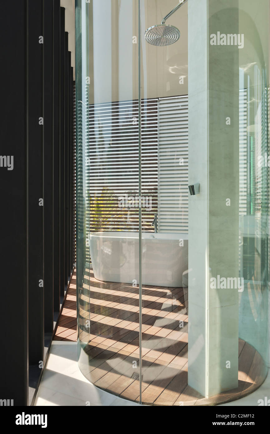 Glass drum shower cubicle in modern bathroom with venetian blinds and patterns of light - Stock Image