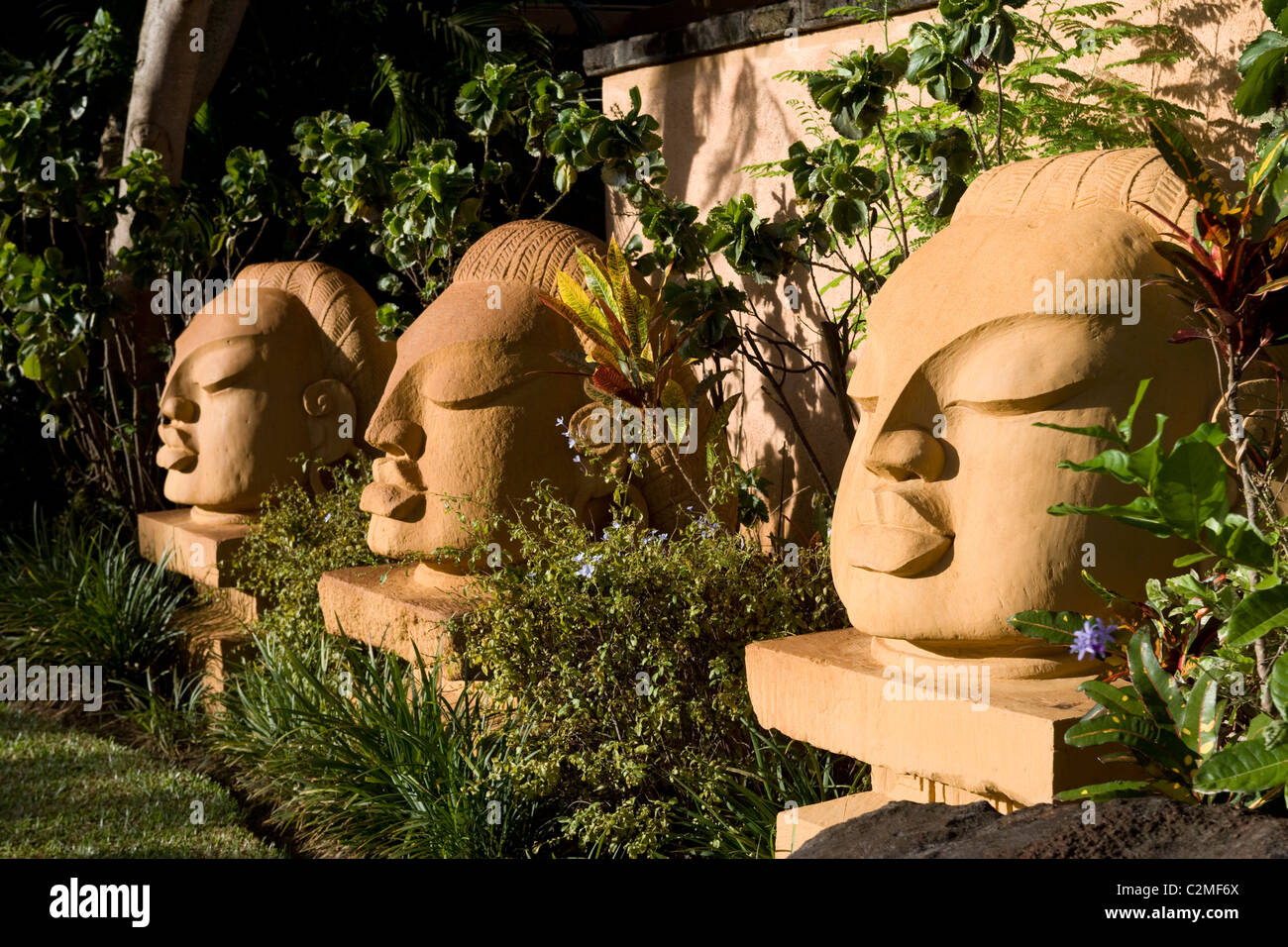 Three sculpted heads in subtropical gardens - Stock Image