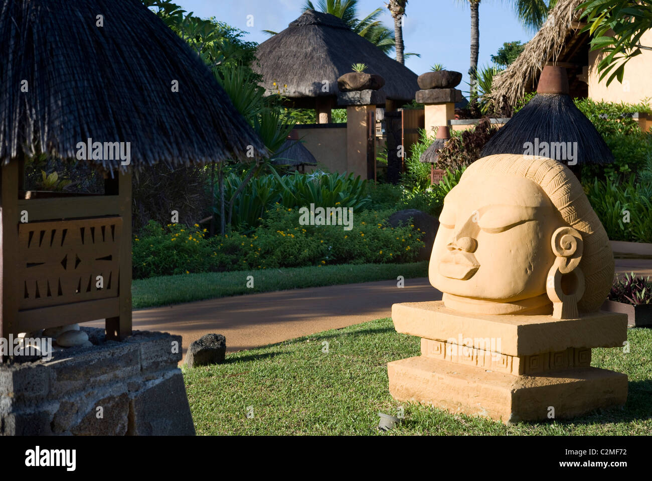 Sub-tropical gardens with large sculptural head at The Oberoi - Stock Image