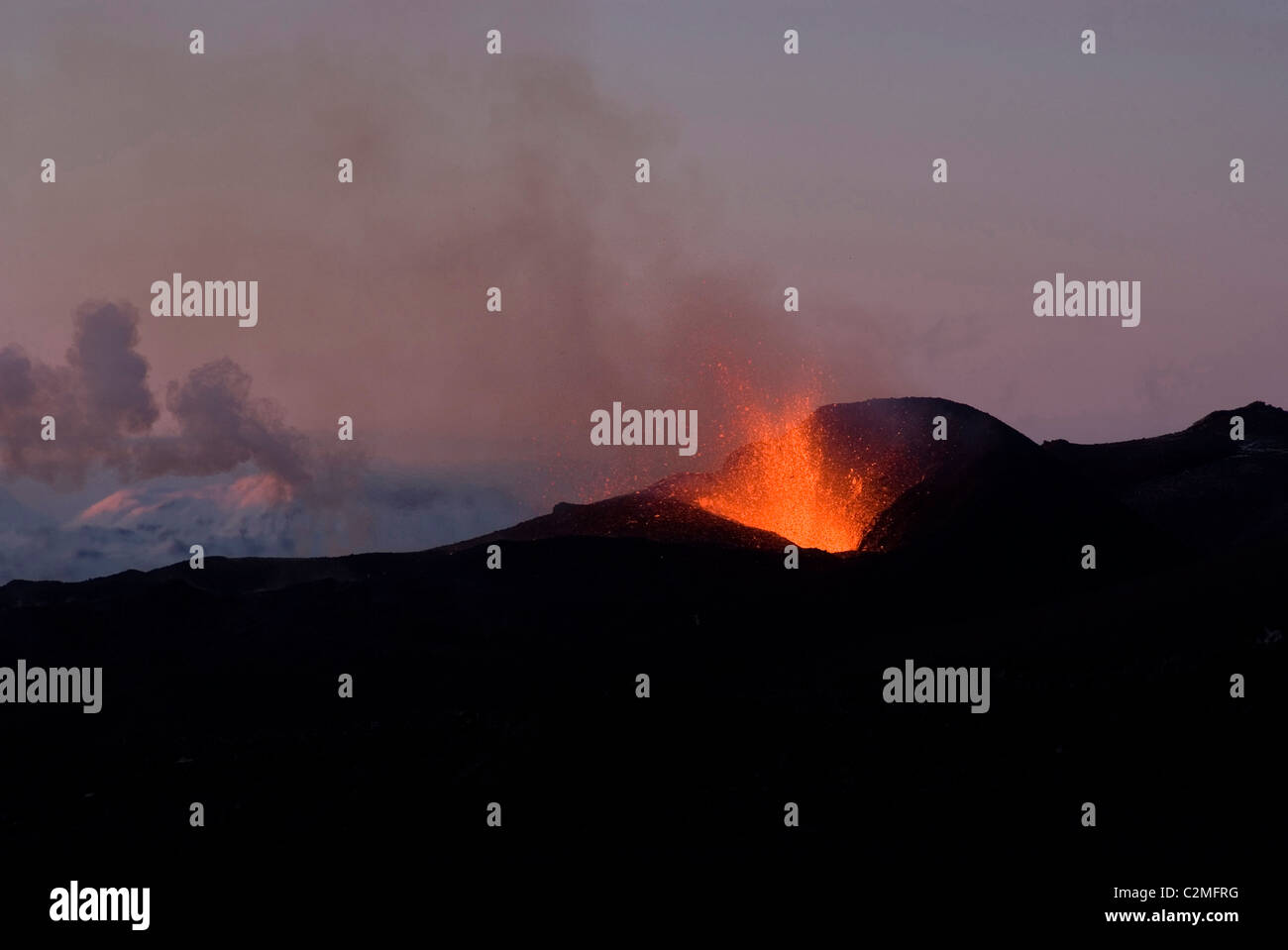 Fountaining lava from Eyjafjallajokull volcano, silhouetted against sunset, Southern Iceland - Stock Image