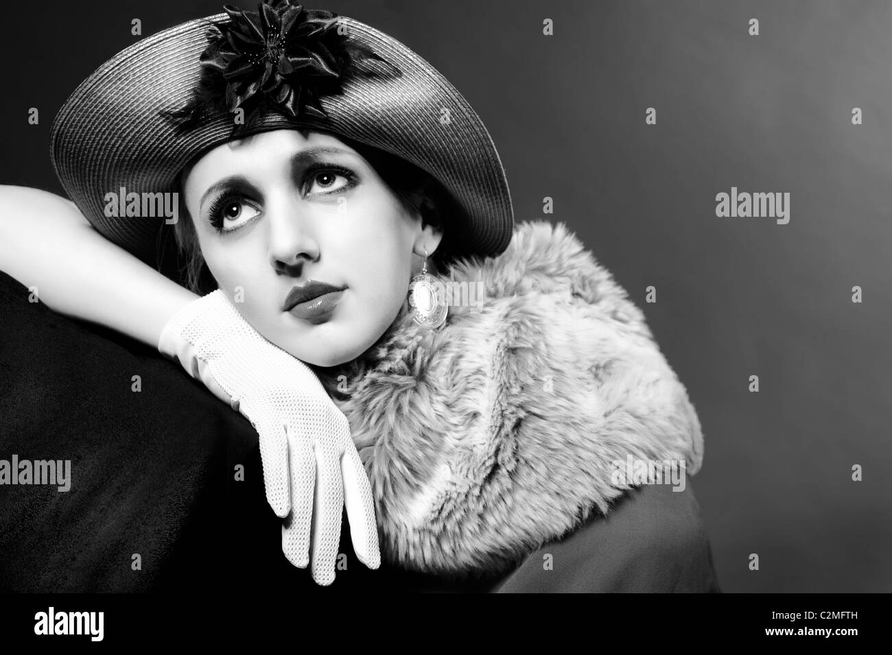 Retro styled fashion portrait of a young woman in hat. Clothing and make-up in vintage 1920s style - Stock Image