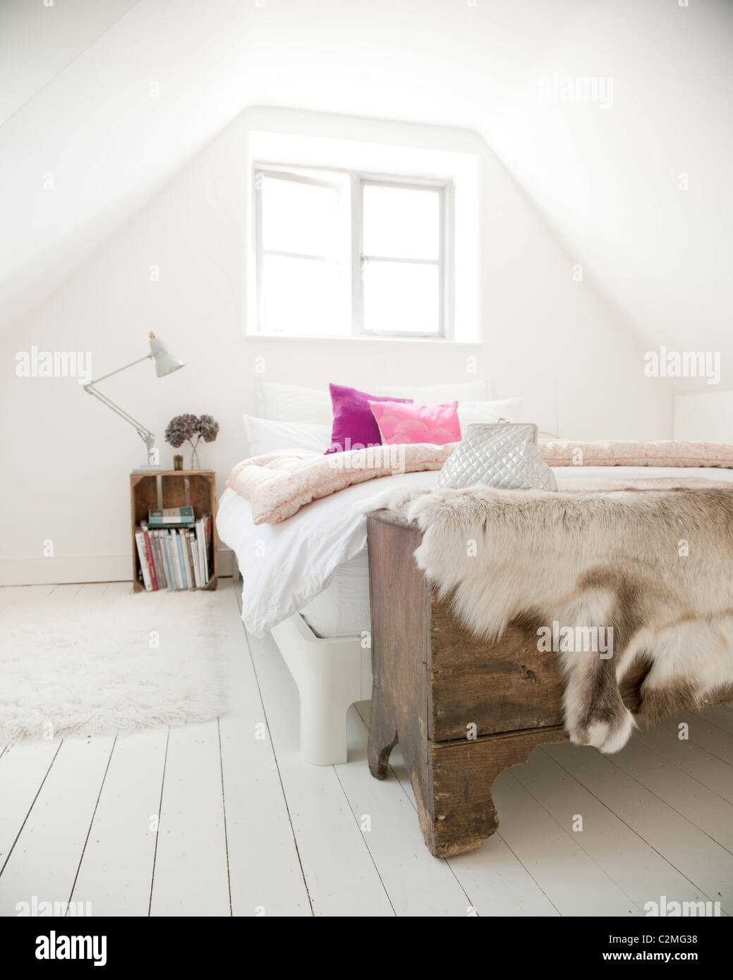 Orchard Cottage shabby chic white attic bedroom with pink cushions - Stock Image