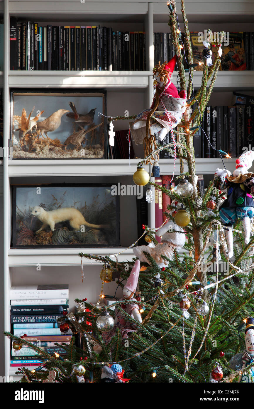 Christmas tree with Jessica Quinn dolls in sitting room with book cases - Stock Image