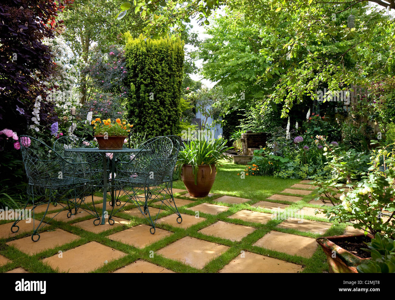 Suburban Garden. Wire garden furniture on checkerboard paving stone and grass amongst lush green planting including - Stock Image