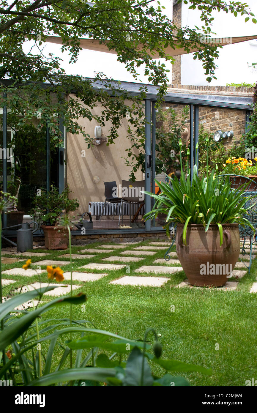 Suburban Garden. Checkerboard paving stone and grass, agapanthus in large terracotta pot, conservatory and sail - Stock Image