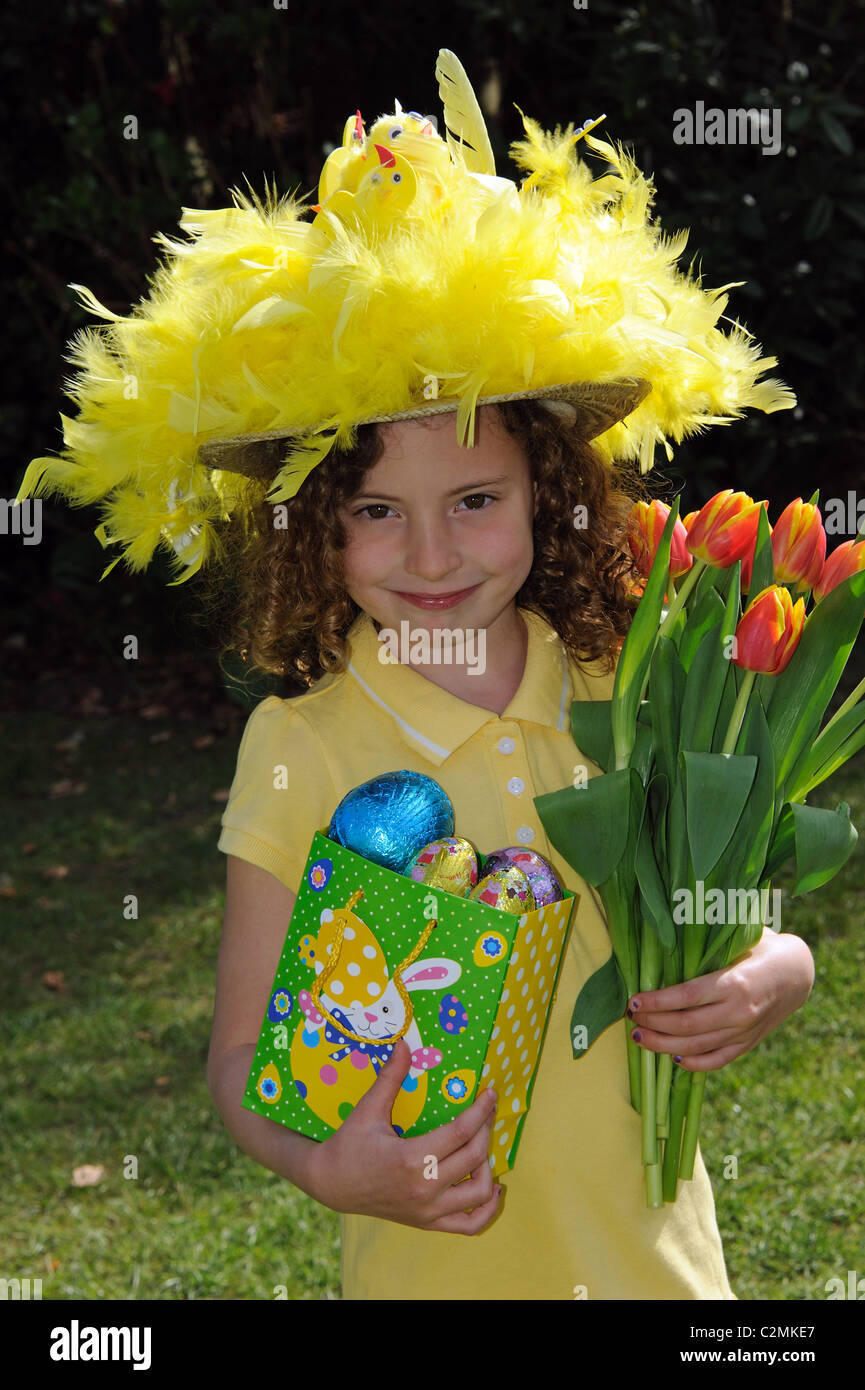 Portrait of a little girl wearing an Easter bonnet and holding a bunch of  red and f4bd62e43d9