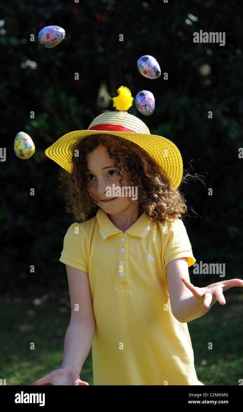 Portrait of a little girl wearing an Easter bonnet and juggling her chocolate eggs - Stock Image