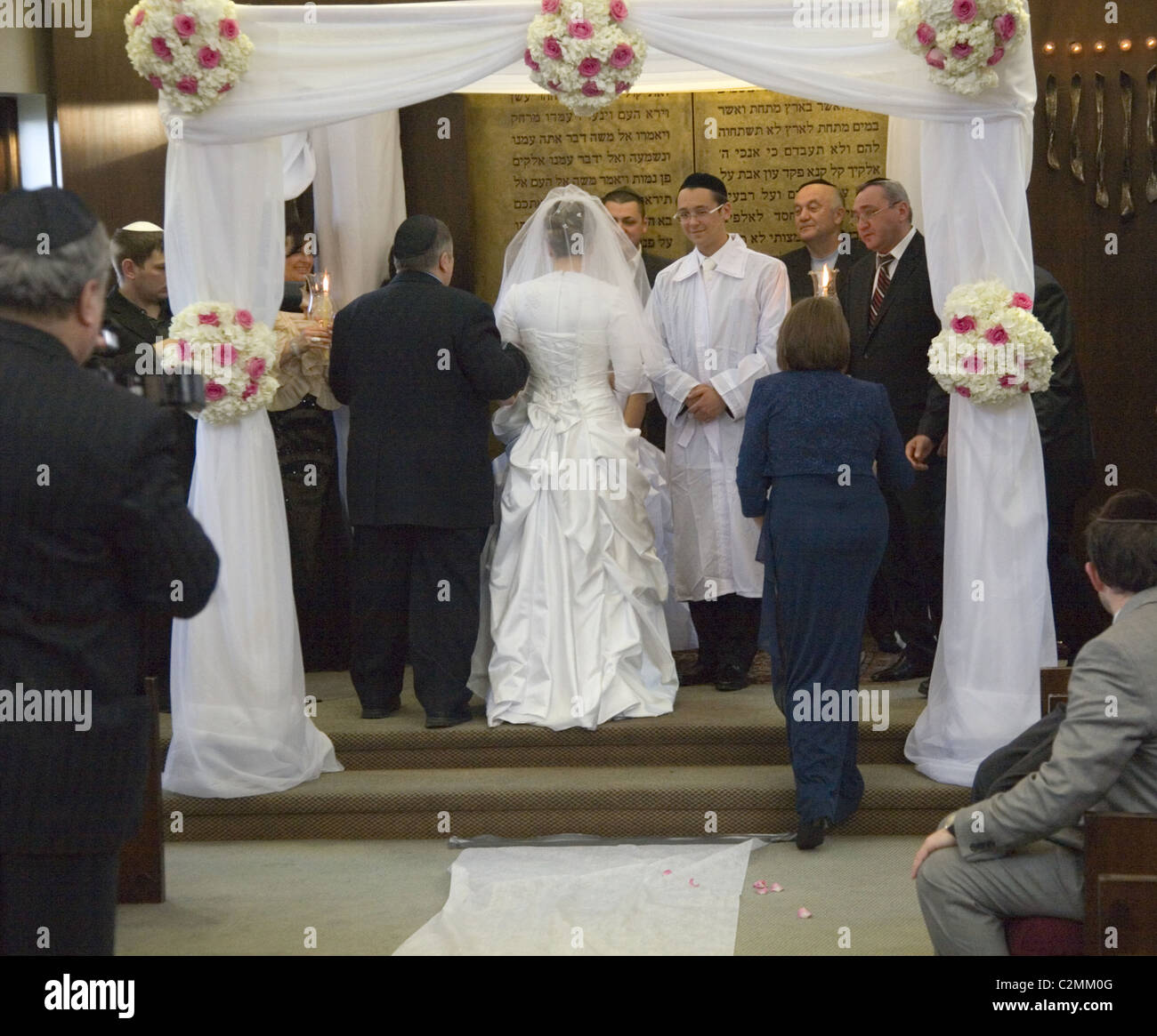 Bride accompanied by her parents meets the groom at an Orthodox Jewish wedding ceremony in Brooklyn, NY. - Stock Image