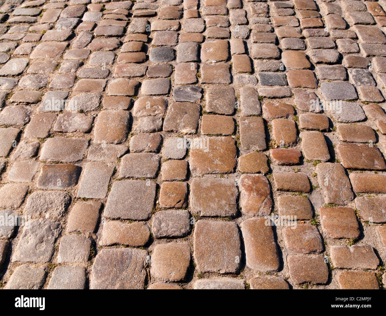 Cobble stones on an old cobbled street close up, UK - Stock Image