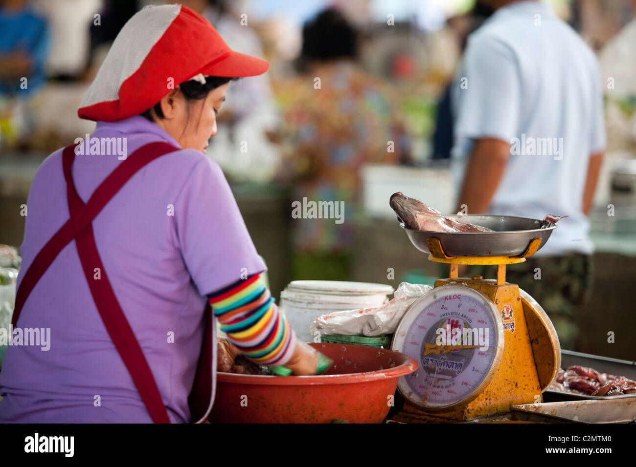 Fish shopkeeper sell the fish by scale in local market Lampang, Thailand - Stock Image