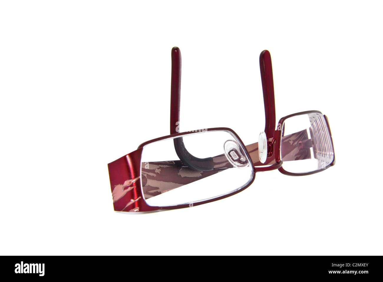 A pair of folded eye glasses on a white background - Stock Image