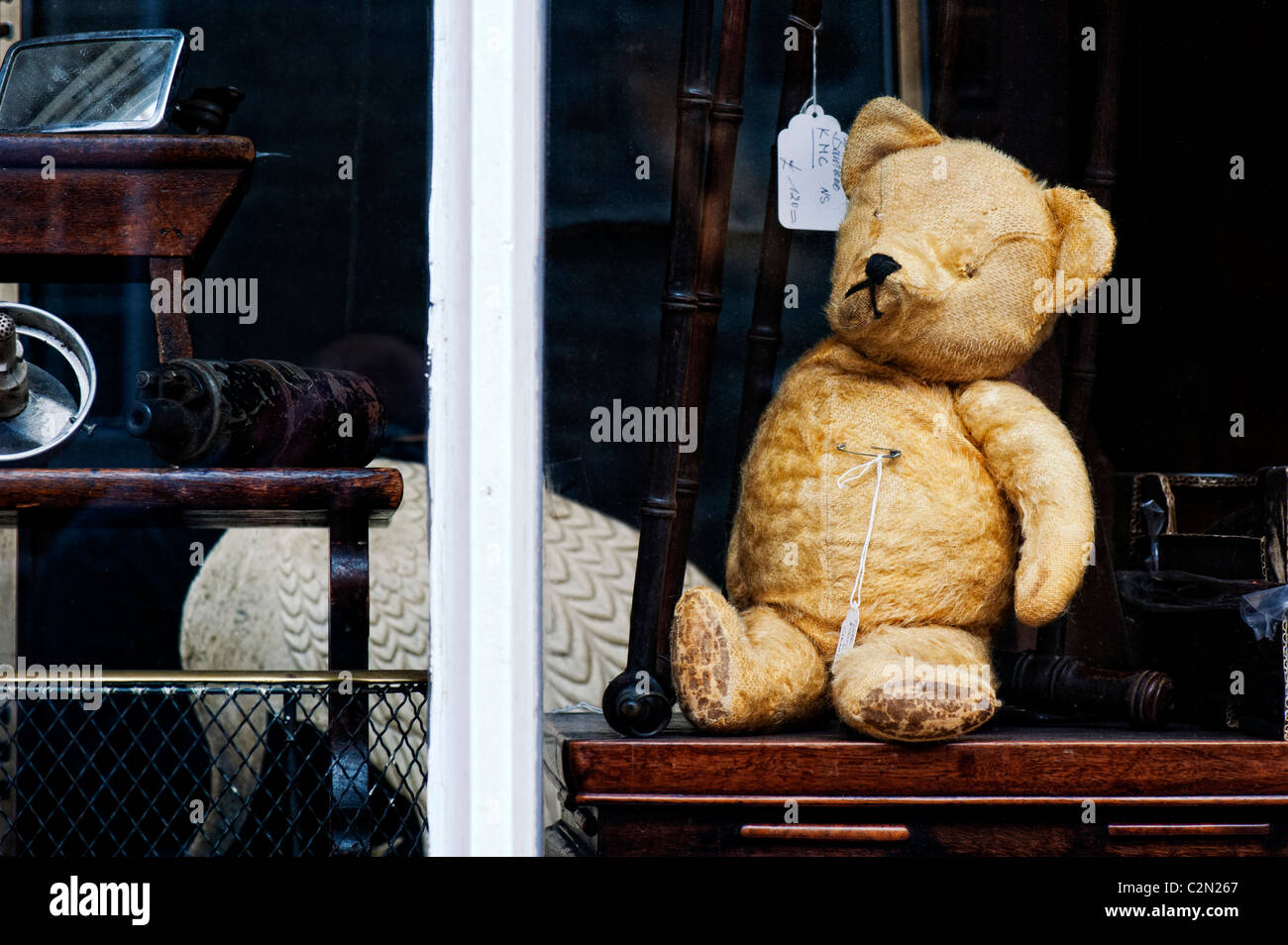 Old worn well loved teddy bear in an antique shop window. Oxfordshire, England Stock Photo