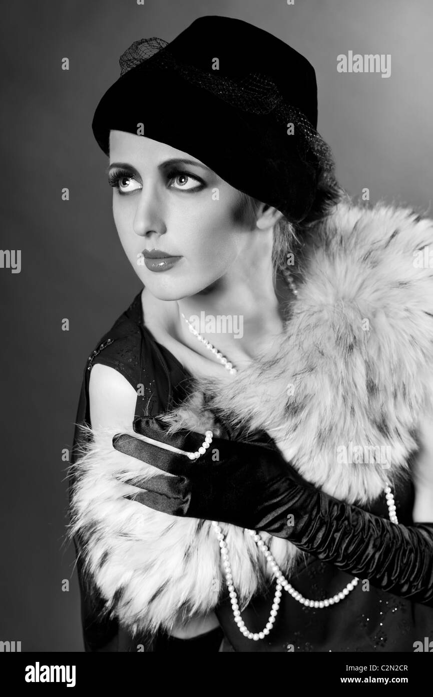 Retro styled fashion portrait of a young woman with pearls. Clothing and make-up in vintage style - Stock Image