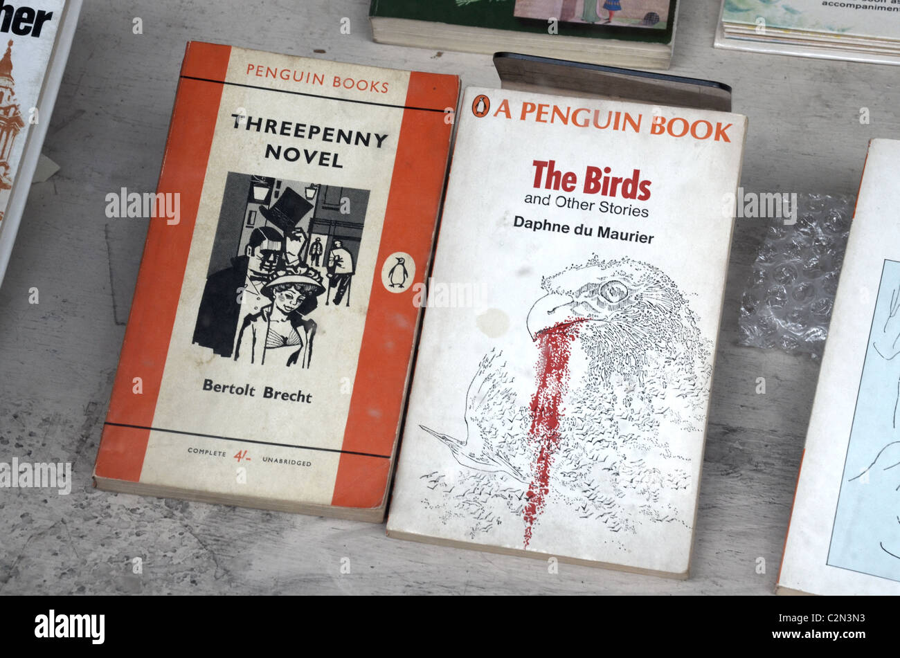 Two vintage Penguin paperbacks by Bertolt Brecht and Daphne du Maurier in a secondhand bookshop window. - Stock Image