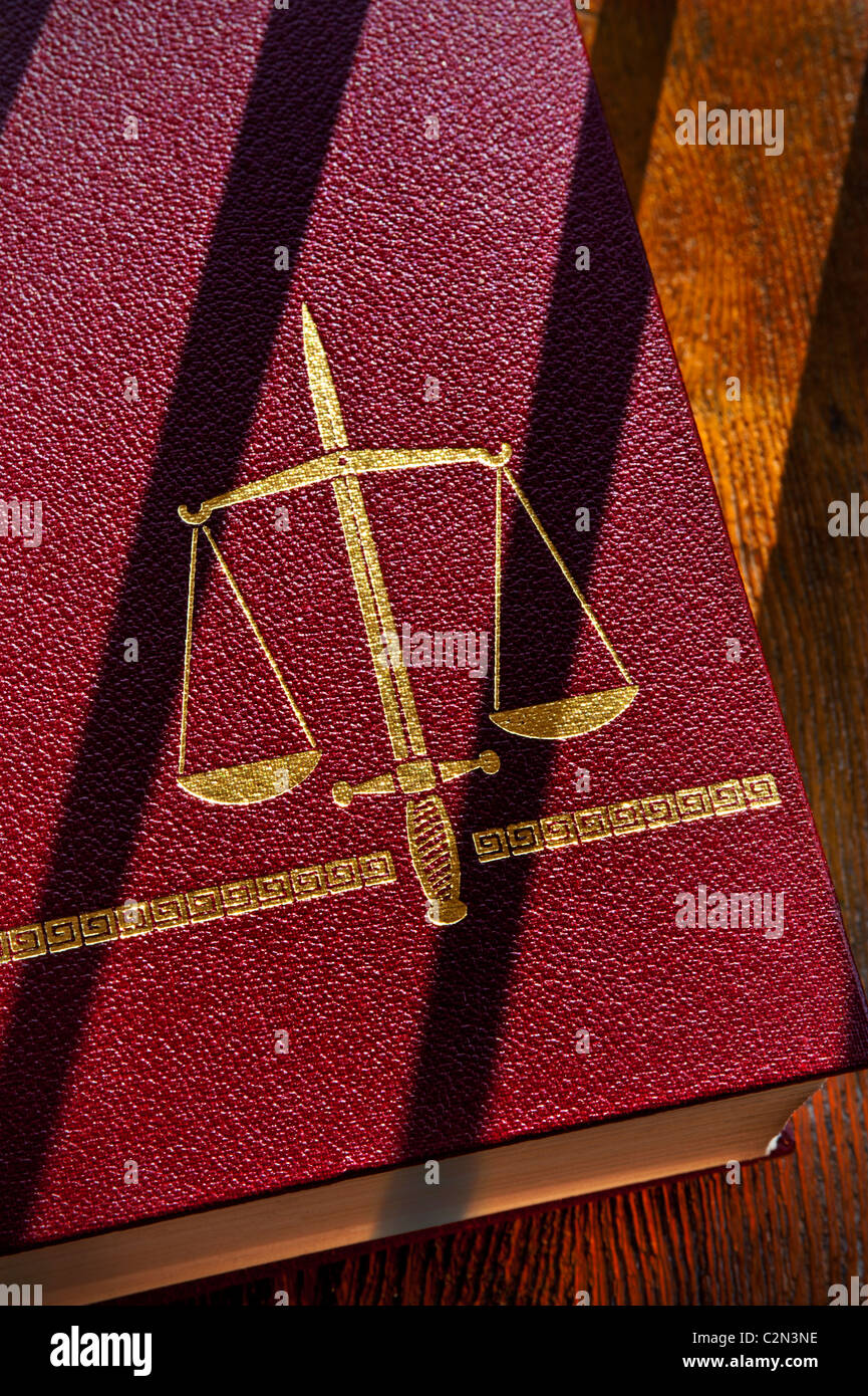 Law concept depicted by a legal book with scales of justice and double edged sword motif with shadows of bars glancing - Stock Image