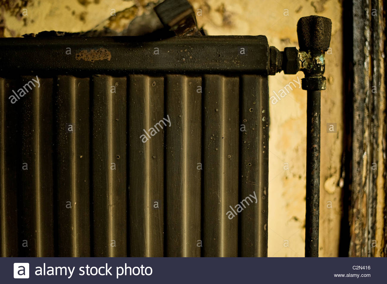 Abandoned fire damage room with a radiator on the Wall - Stock Image