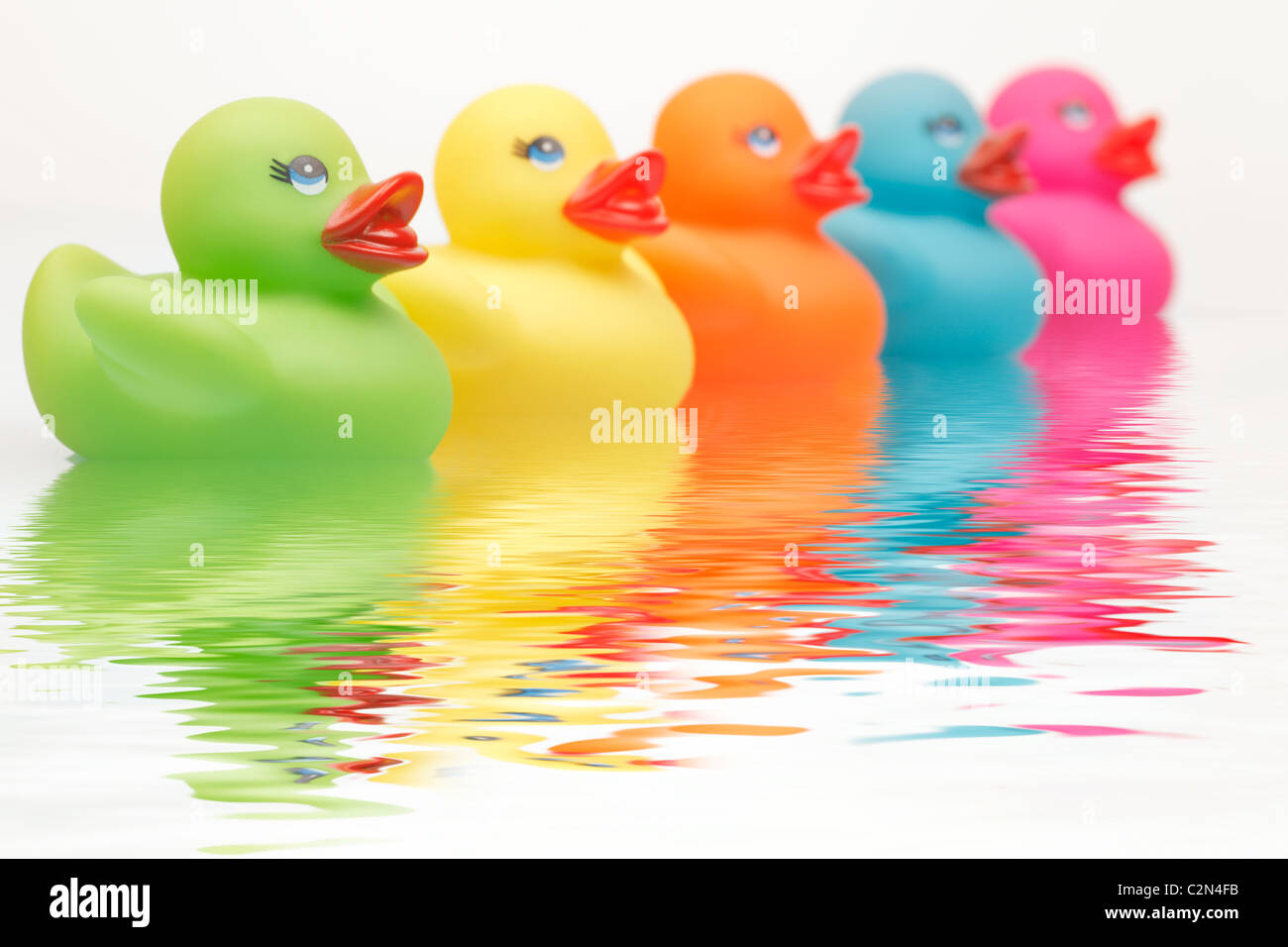 Colourful Rubber Ducks with water ripples - Stock Image