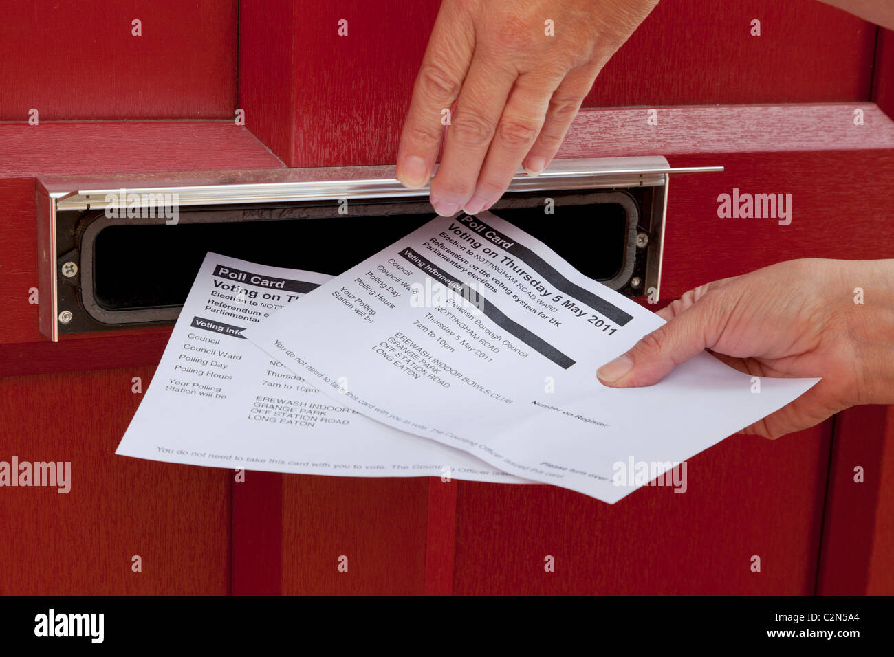 Polling cards being pushed through a front door letter box for the Av Referendum on May 5th 2011 England UK - Stock Image