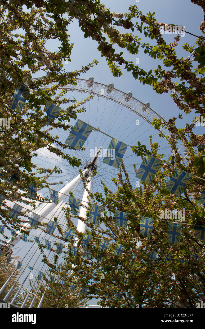 The London Eye Millennium wheel taken from underneath trees and Union Jack flags at an unusual angle - Stock Image