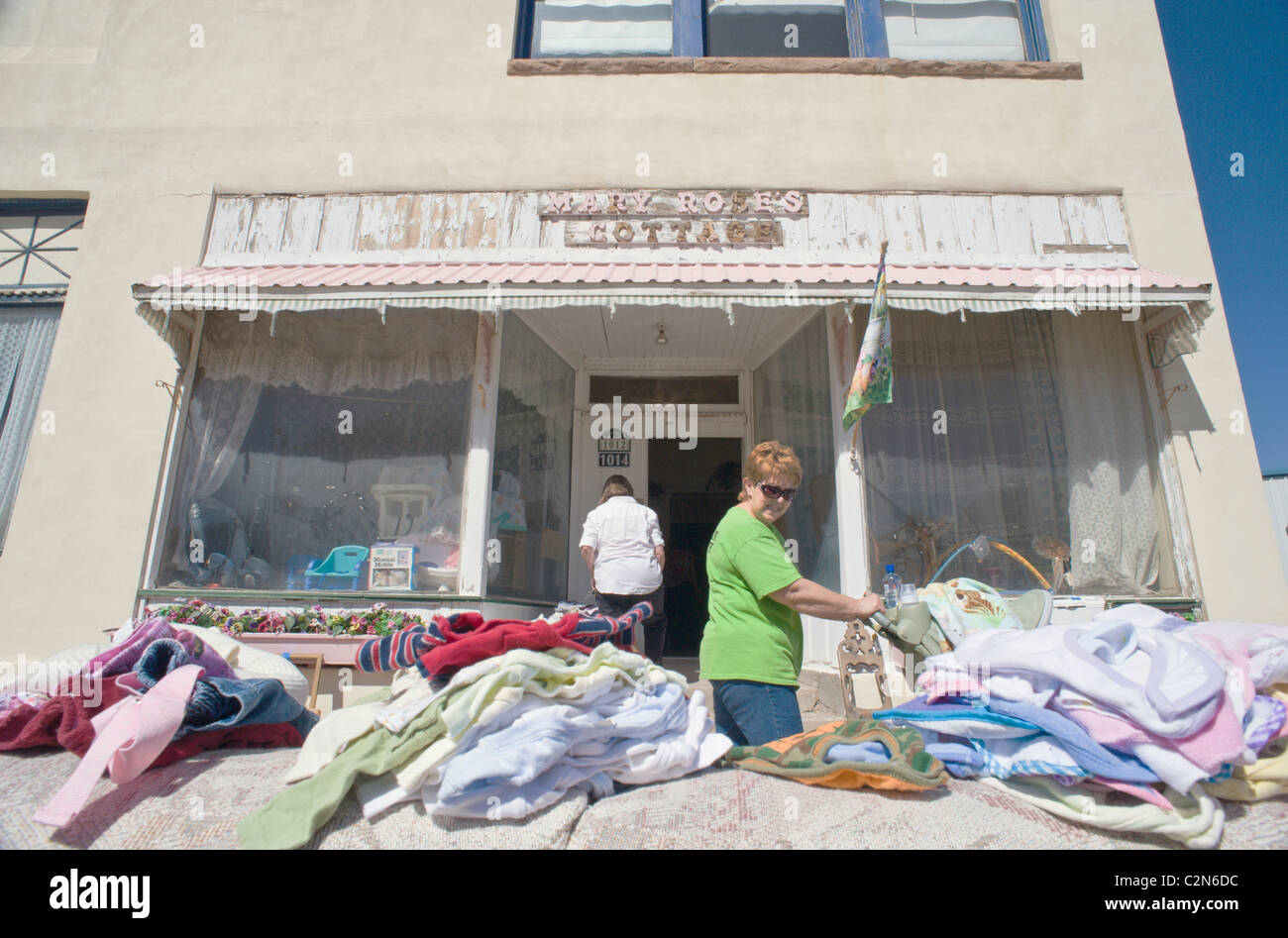 A woman pushing a baby stroller (pram) looks over the goods at a small town rummage sale (jumble sale), in Carrizozo, - Stock Image