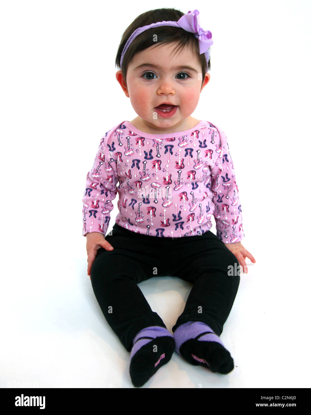 Happy baby sitting up in studio. - Stock Image