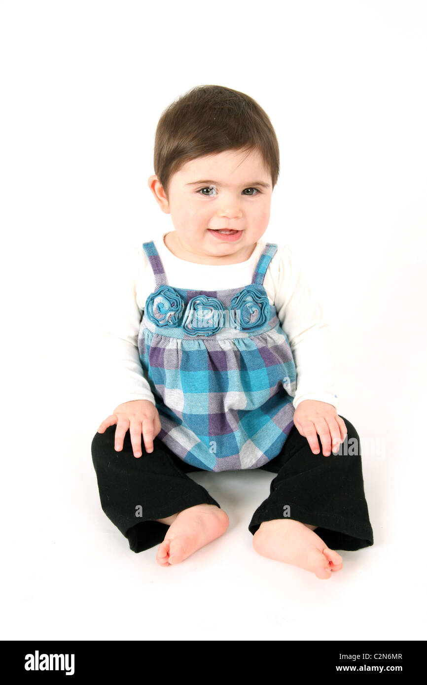Baby sitting up in studio on white - Stock Image
