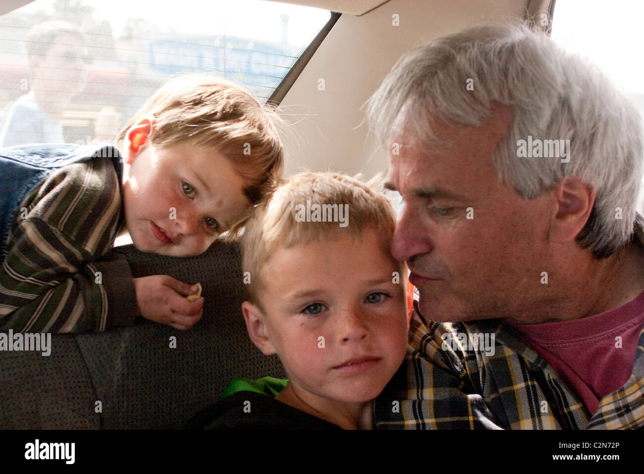 A father enjoying some quiet family time in the car with his two sons. - Stock Image