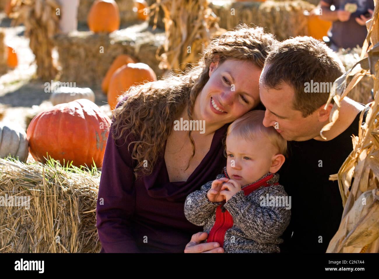 A family enjoying itself at a pumpkin patch. - Stock Image