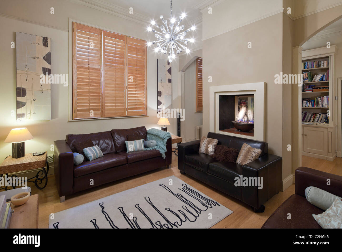 Neutral family sitting room with wooden floor, wooden shutters & leather sofas - Stock Image