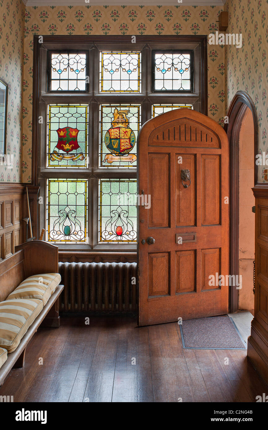 Entrance Hall and stained glass window with heraldic crests, arched door and wooden settke - Stock Image