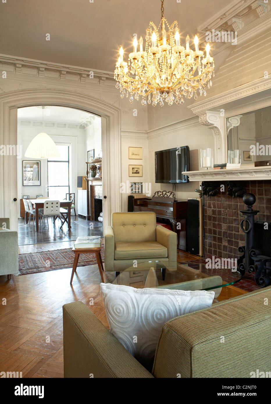 Brooklyn Brownstone Interior. Linked Living Room And Dining Room With Lit  Chandelier, Parquet Flooring, Brick Fireplace And
