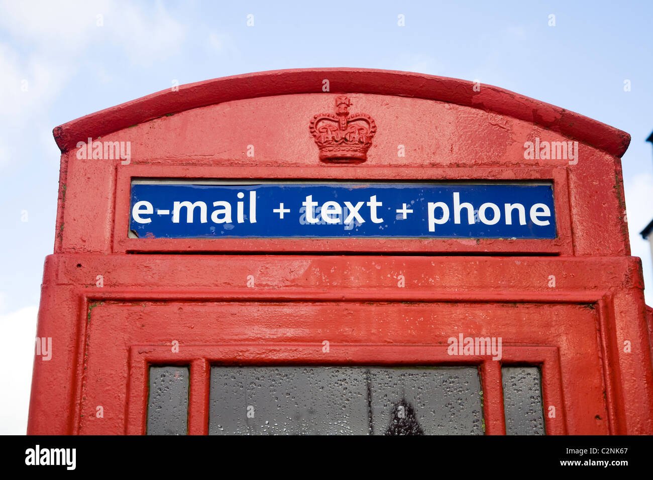 New modern services – email / e mail / text / texting from public telephone / phone in original red / call box. - Stock Image
