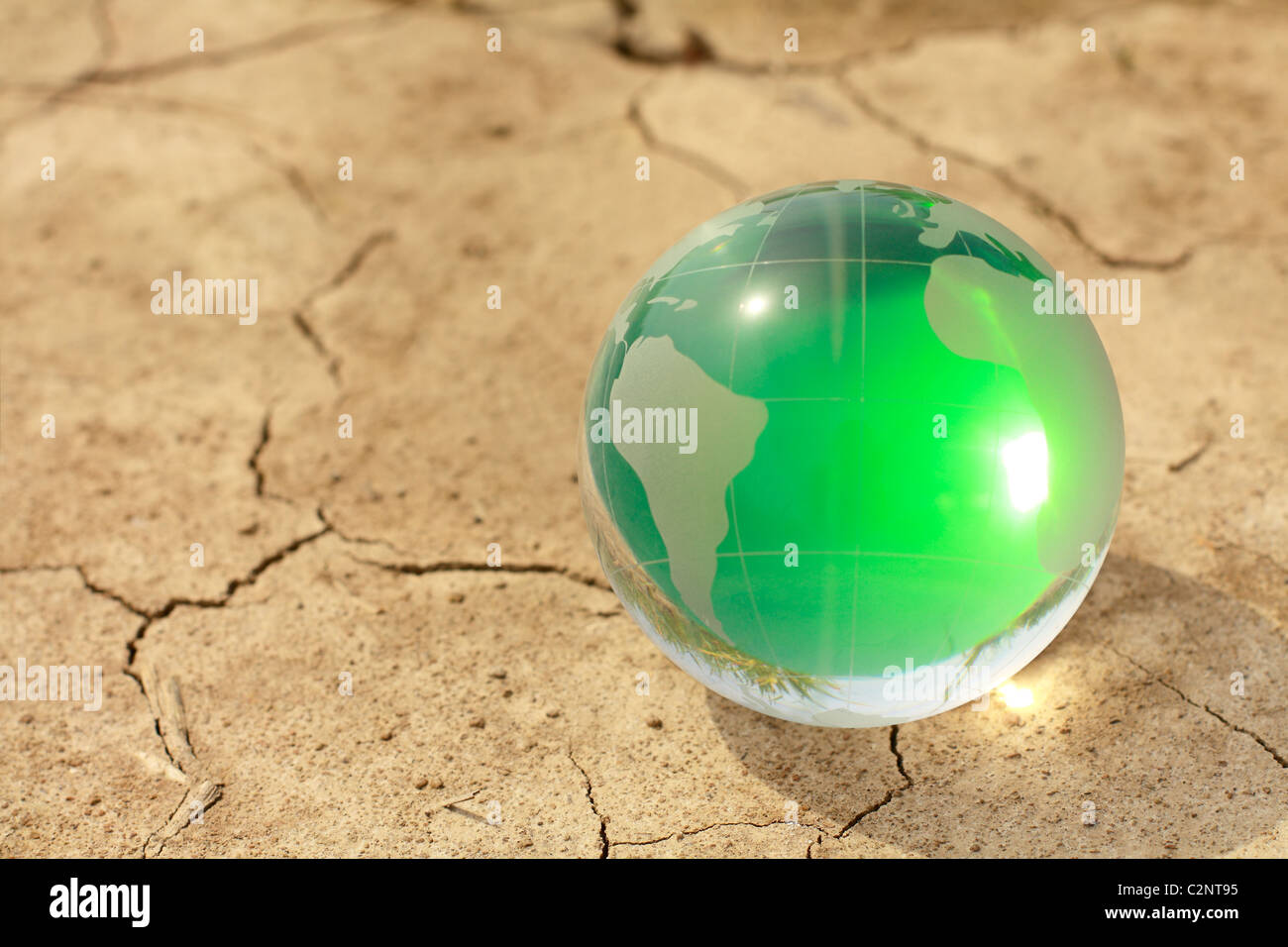 glass on the planet parched cracked earth - Stock Image