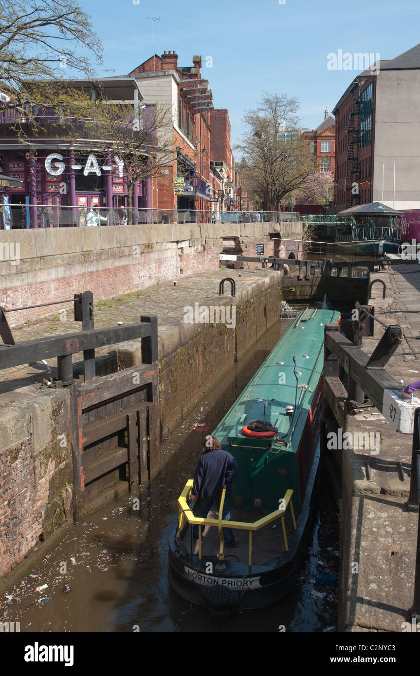 Canal boat going entering lock on the Rochdale canal in the Village district of central Manchester. - Stock Image