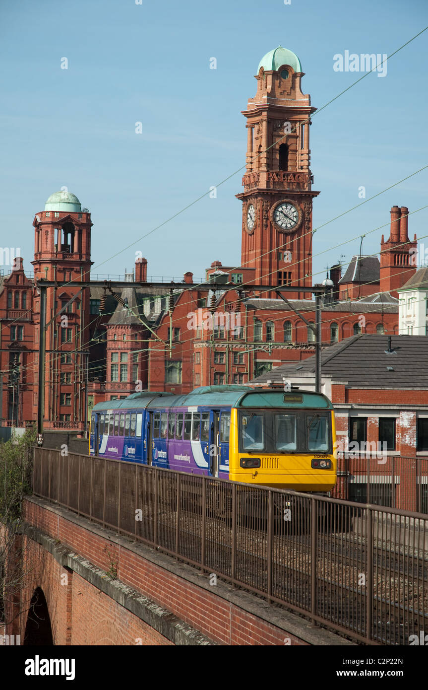 Northern Rail train traveling through the centre of Manchester, the Palace Hotel in the background. - Stock Image