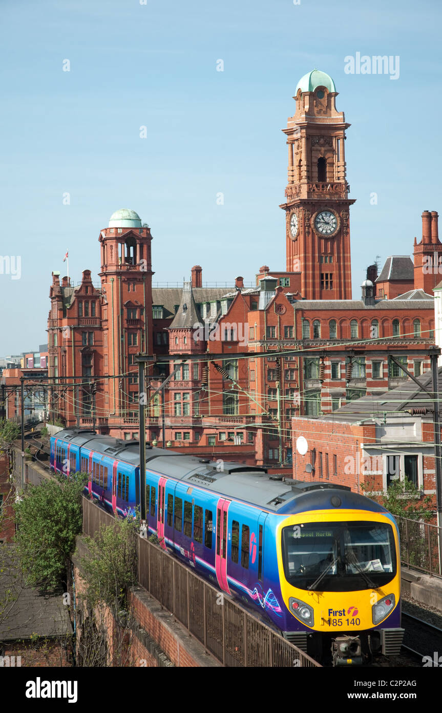 First train city centre Manchester, with the clock tower of the Palace Hotel in the background. - Stock Image