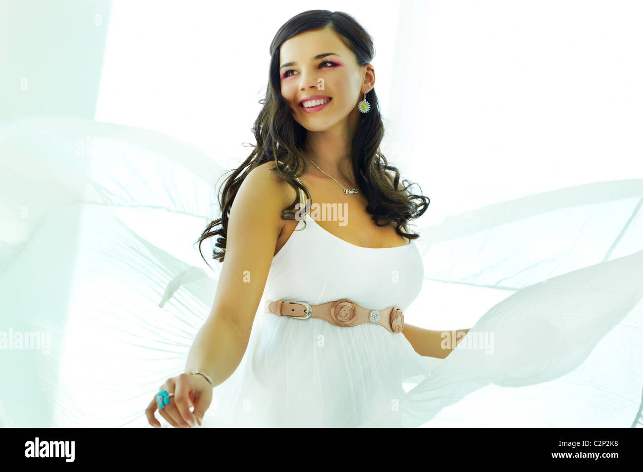 Happy woman in white dress whirling - Stock Image