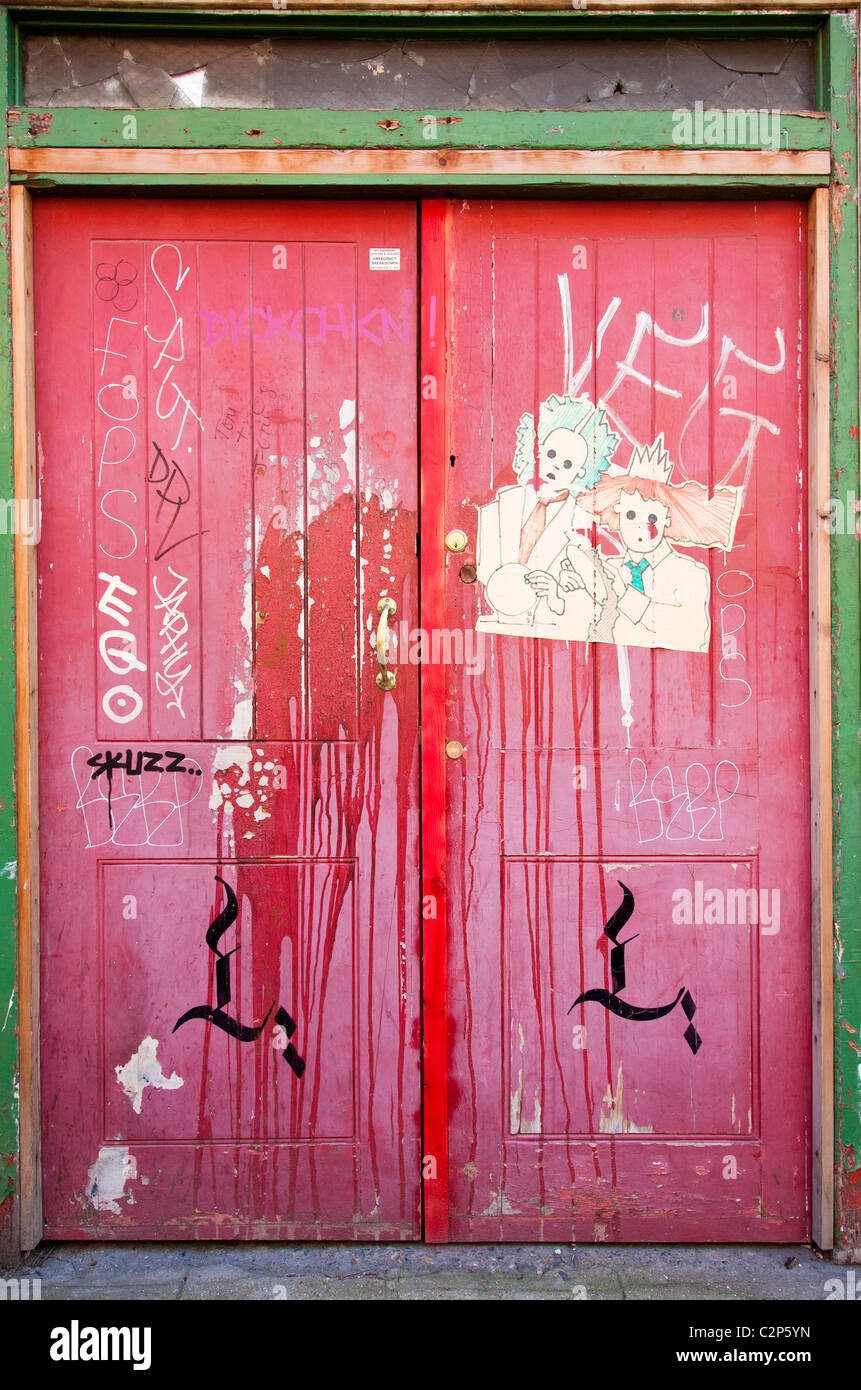 A pair of wooden red doors with graffiti just off Brick Lane London, E1, UK - Stock Image