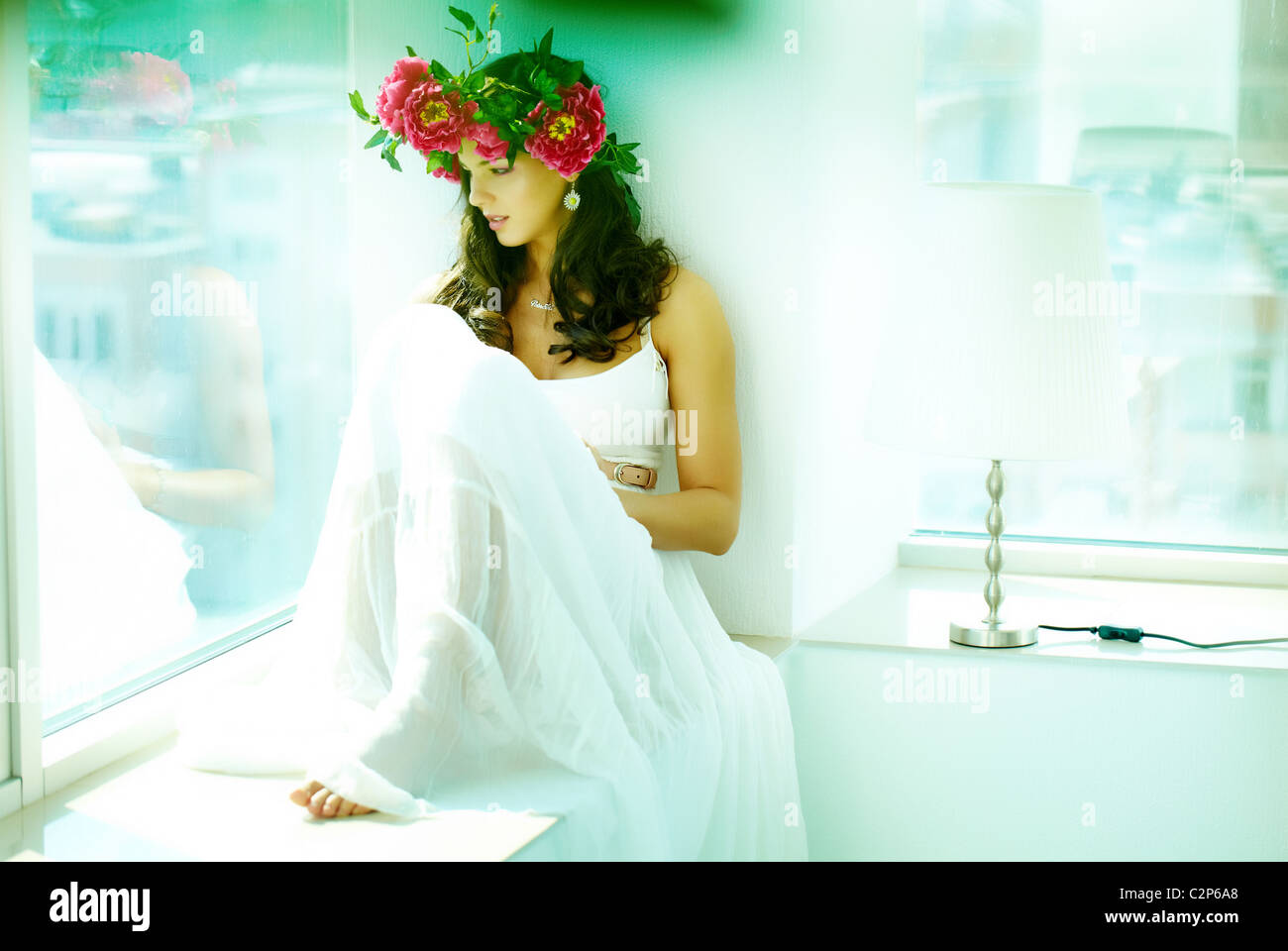 Beautiful woman in white dress sitting on window sill and looking through glass Stock Photo