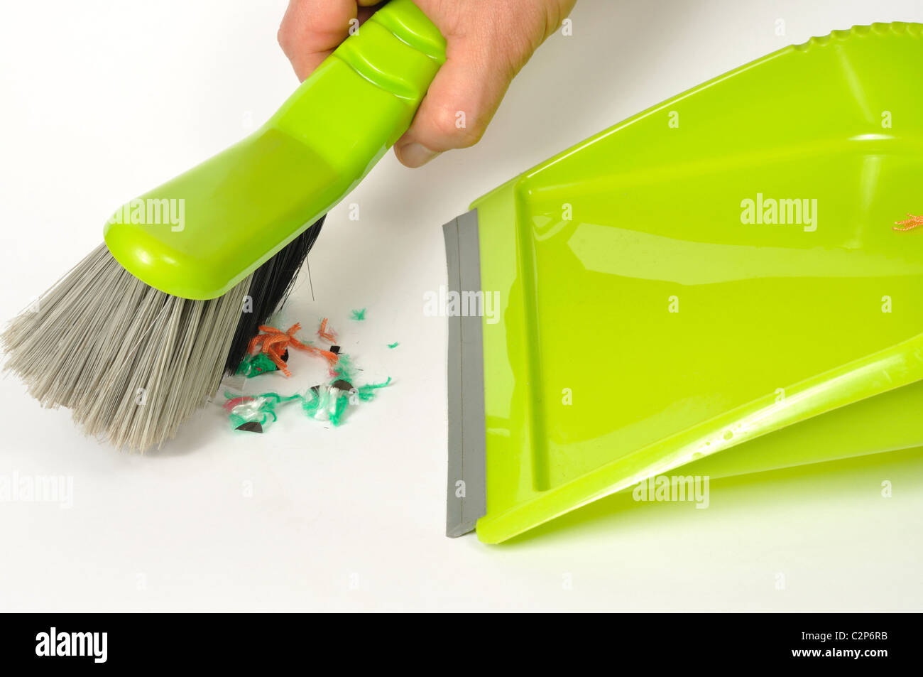 Green brush and dustpan with some garbage on white background - Stock Image