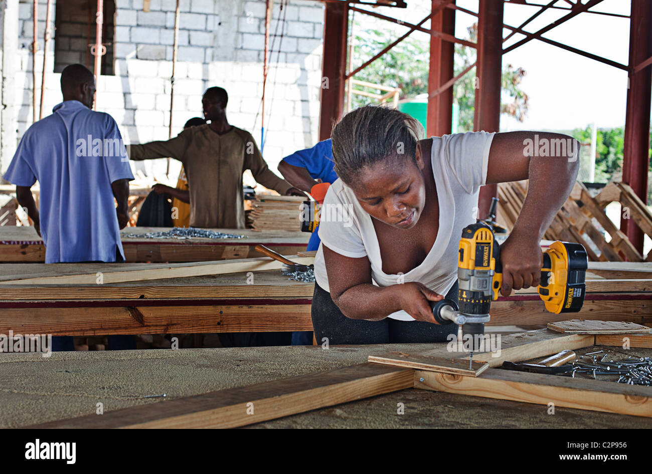 A woman working with mechanical tool  for Habitat for humanity house buiding  NGO project, Leogane, Haiti - Stock Image