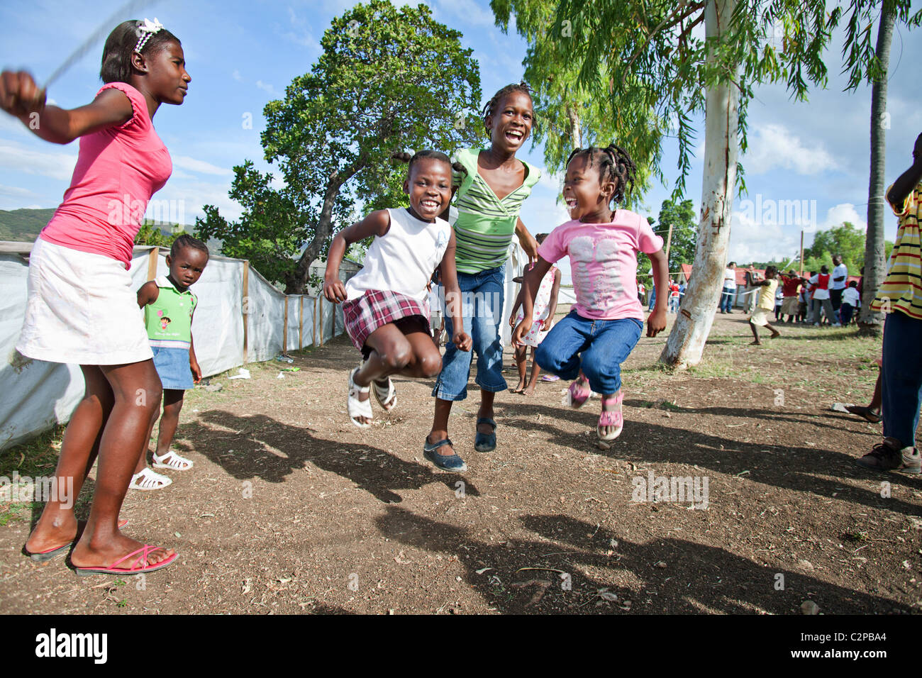Haitian girls skipping rope in an NGO education camp , Petit Goave Haiti. - Stock Image