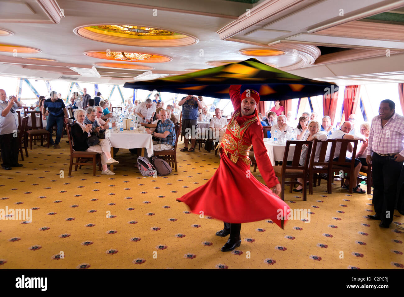 A WHIRLING DERVISH ENTERTAINING TOURISTS ON A NILE RIVER BOAT, - Stock Image