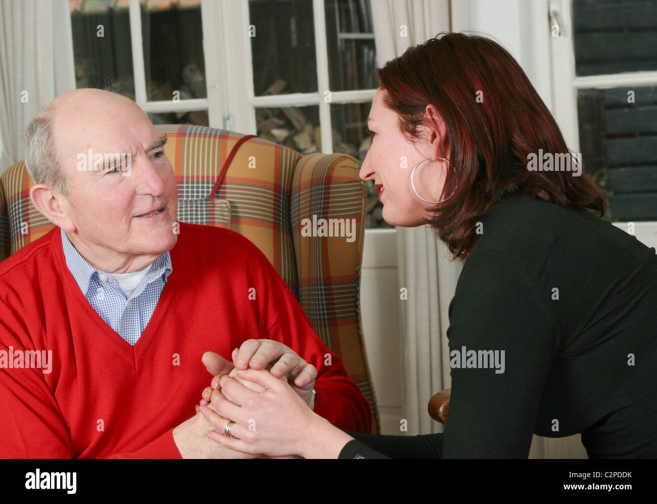 Woman looking after man older or voluntary worker - Stock Image