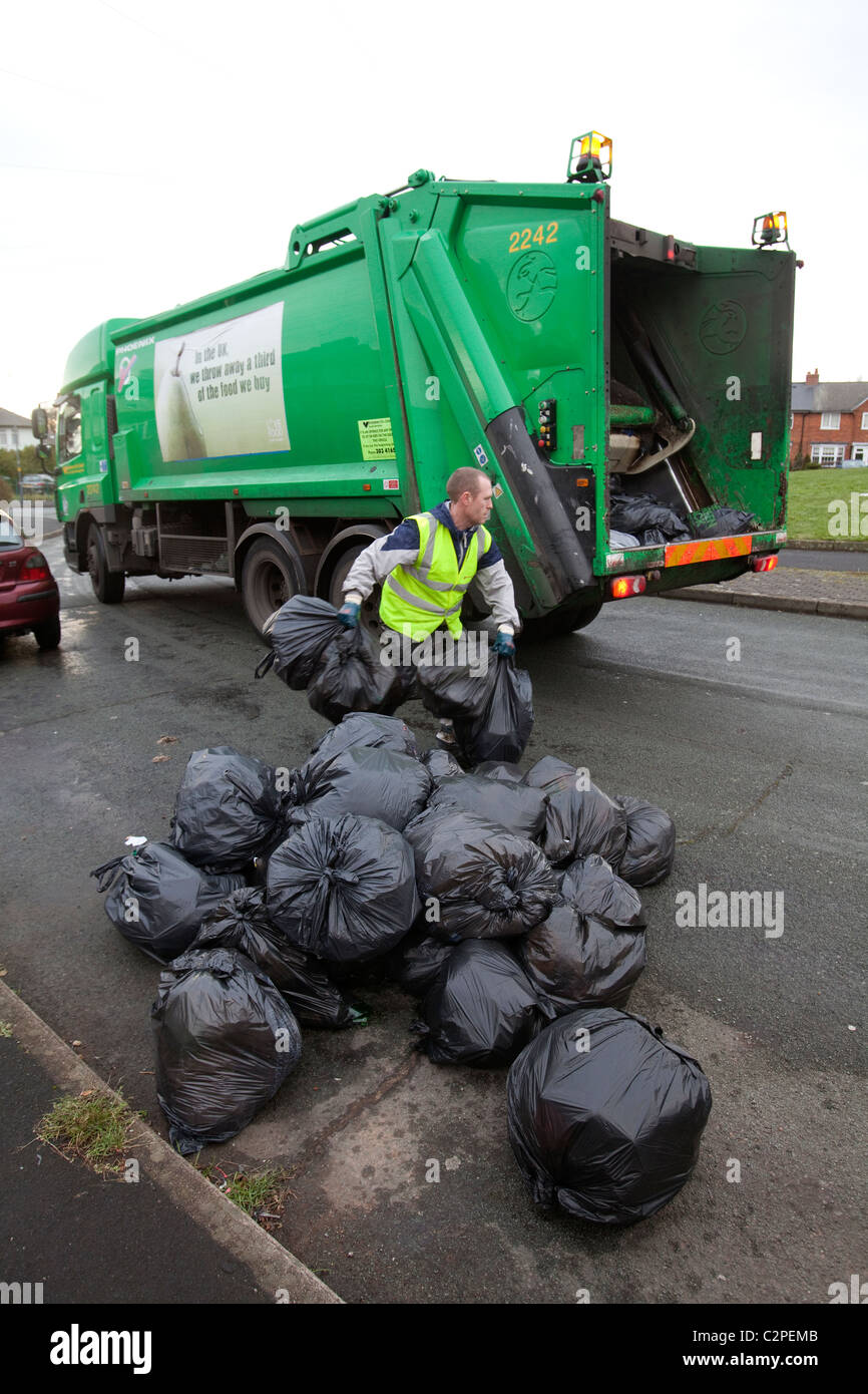 Bags of household rubbish being picked up by a refuse collector in Birmingham, UK - Stock Image