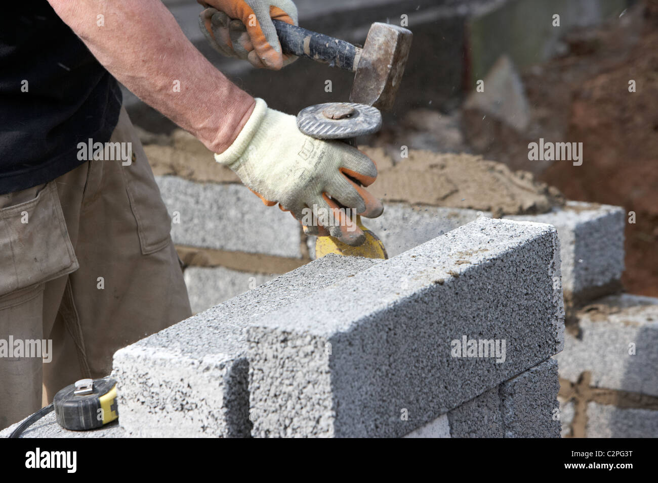 Bricklayer Using A Hammer And Brick Chisel Bolster To Cut